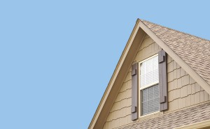 Roof gable with blue sky and window shutters